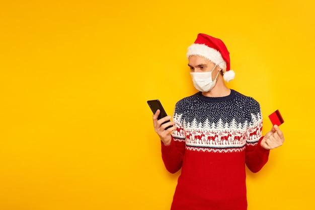Aufgeregter mann weihnachtspullover rote weihnachtsmütze mit telefon-plastikkarte in den händen kauft online ein