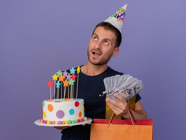 Aufgeregter schöner kaukasischer mann, der geburtstagskappe hält, hält geburtstagskuchenpapier-einkaufstasche-geschenkbox und geld, das seite lokalisiert auf lila hintergrund mit kopienraum betrachtet