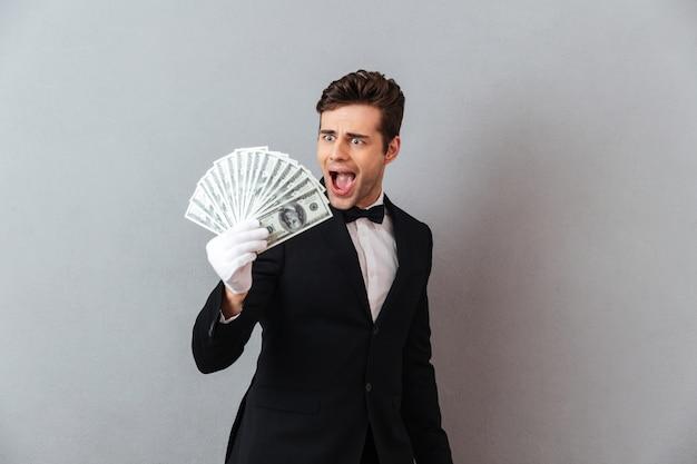 Aufgeregter schreiender junger kellner, der geld hält.