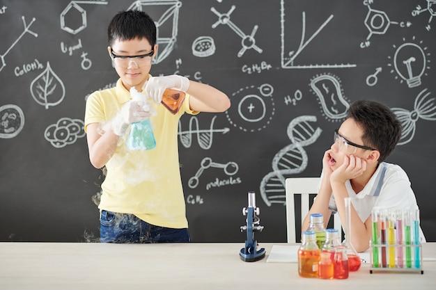 Aufgeregter schuljunge in schutzbrille, der den mund öffnet, wenn er seinen klassenkameraden betrachtet, der rauchende bunte chemische flüssigkeiten mischt