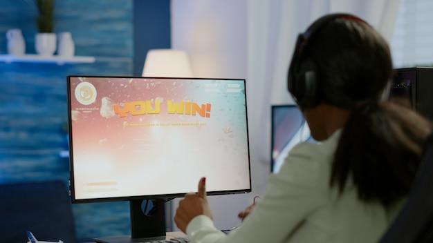 Aufgeregter schwarzer e-sport-spieler, der den meisterschaftssieg feiert, frau gewinnt weltraum-shooter-videospiel. pro cyber-gaming-online-turnier-live-streaming-meisterschaft mit leistungsstarkem rgb-computer