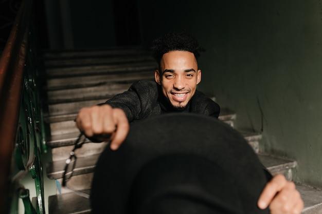Aufgeregter schwarzer mann, der auf treppen sitzt. porträt des fröhlichen afrikanischen modells, das hut in händen hält.