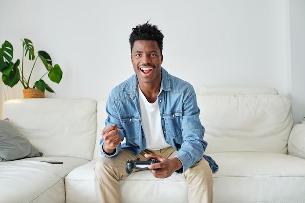 Aufgeregter schwarzer mann, der ein videospiel mit joystick auf der couch spielt