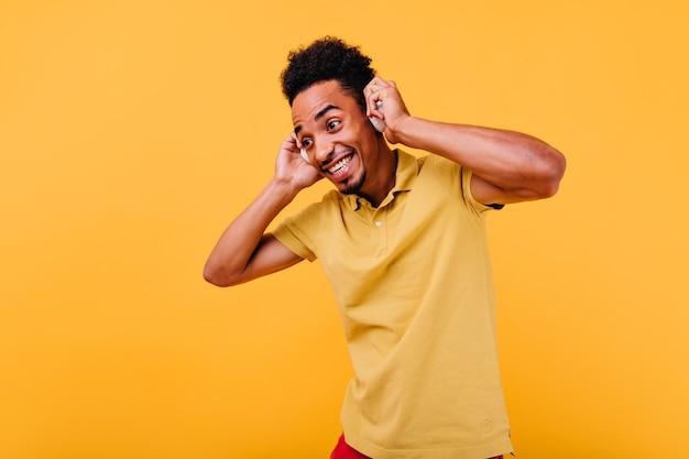 Aufgeregter schwarzer mann in großen kopfhörern lustiges aufstellen. fröhlicher kerl mit dunklem haar, der lieblingslied genießt.