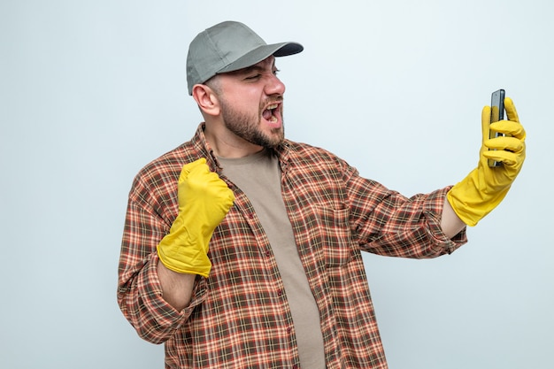 Aufgeregter slawischer putzmann mit gummihandschuhen, der die faust hält und auf das telefon schaut