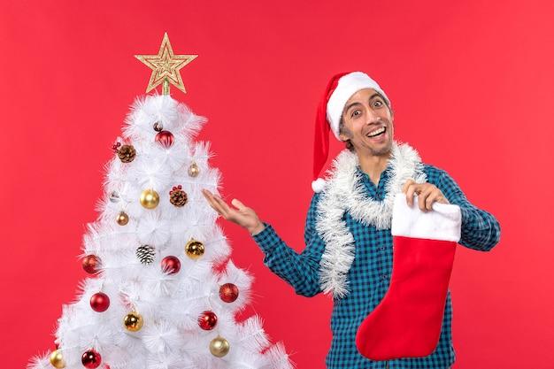 Aufgeregter stolzer glücklicher junger mann mit weihnachtsmannhut in einem blau gestreiften hemd und in der weihnachtssocke
