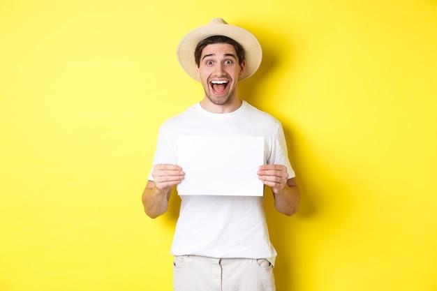Aufgeregter tourist, der ihr logo oder zeichen auf leerem stück papier zeigt, erstaunt lächelt und vor gelbem hintergrund steht.