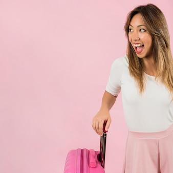 Aufgeregter tragender reisekoffer der jungen frau gegen rosa hintergrund