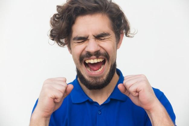 Aufgeregter überglücklicher glückspilz, der vor freude schreit