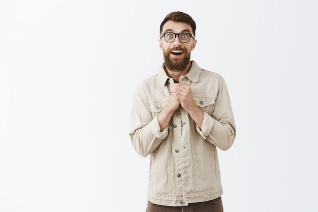 Aufgeregter und fröhlicher bärtiger mann in gläsern, der gegen die weiße wand posiert