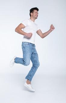 Aufgeregter und glücklicher junger mann springt und schreit in weißen t-shirts und jeans auf weißem hintergrund.