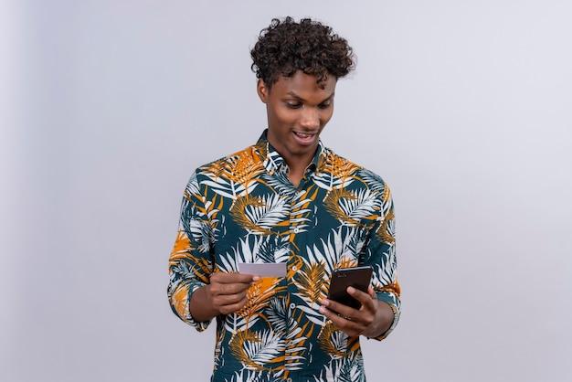 Aufgeregter und überraschter junger gutaussehender dunkelhäutiger mann mit lockigem haar im blattbedruckten hemd, das sein telefon betrachtet, während kreditkarte hält