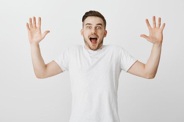 Aufgeregter und überraschter junger mann, der die hände hebt und nach luft schnappt, erstaunt über große neuigkeiten