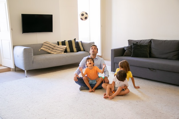 Aufgeregter vater, der mit kindern auf teppich sitzt und spielt. netter verspielter junge, der ball wirft und ihn ansieht. schöne kinder spielen mit papa zu hause. konzept für kindheit, spiel und vaterschaft