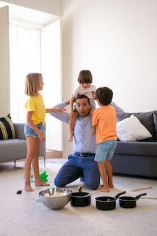 Aufgeregter vater, der spaß mit kindern im wohnzimmer hat. glücklicher vater, der sohn auf schultern hält. entzückendes mädchen und junge, die nahe ihnen stehen. pfannen und schüssel für wild. kindheits-, wochenend- und heimkonzept