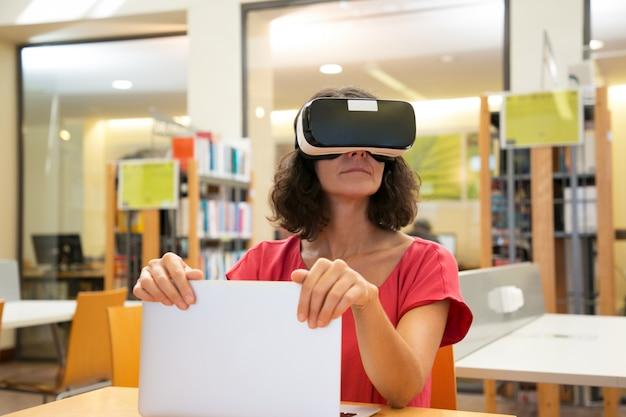 Aufgeregter weiblicher bibliotheksbenutzer, der vr-simulator verwendet
