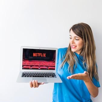 Aufgeregter weiblicher darstellender laptop mit netflix-logo