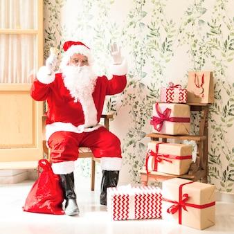 Aufgeregter weihnachtsmann, der auf stuhl nahe bei geschenken sitzt