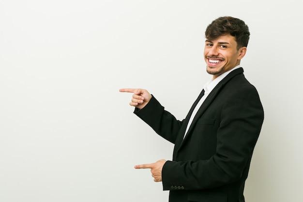 Aufgeregter zeigen des jungen hispanischen mannes des geschäfts mit den zeigefingern weg.