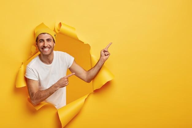 Aufgeregter zufriedener junger mann im lässigen outfit, zeigt etwas großes auf leerzeichen