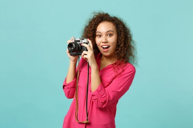 Aufgeregtes afrikanisches mädchen in freizeitkleidung, das ein foto auf einer retro-vintage-fotokamera macht, die auf blau-türkisem wandhintergrund im studio isoliert ist. menschen aufrichtige emotionen lifestyle-konzept. kopieren sie platz.