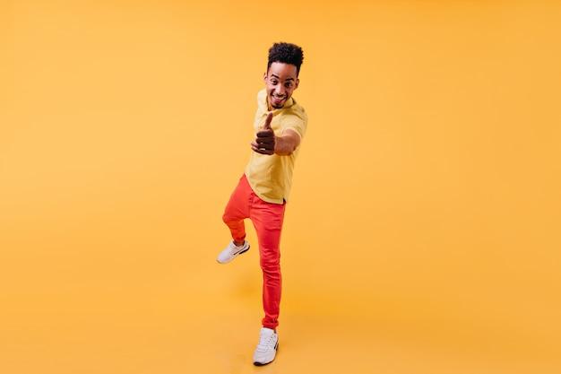 Aufgeregtes afrikanisches männliches modell, das auf einem bein steht und lacht. porträt des erstaunlichen lächelnden jungen mannes trägt weiße turnschuhe.