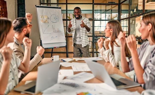 Aufgeregtes afrikanisches und kaukasisches business-team, motiviert durch sieg, leistung oder gute leistung