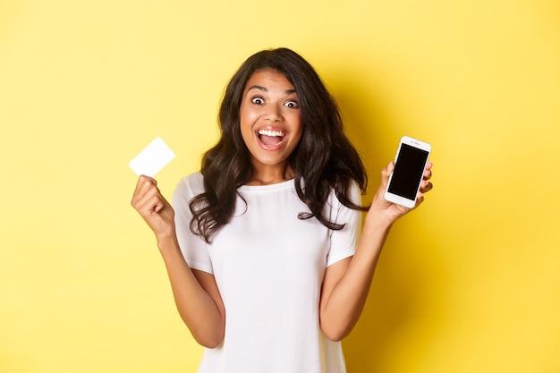 Aufgeregtes afroamerikanisches weibliches modell, das smartphonebildschirm und kreditkarte zeigt