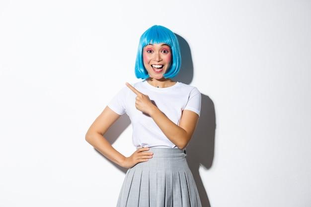 Aufgeregtes asiatisches mädchen, das lächelt und finger in der oberen linken ecke zeigt, ihr logo oder banner blau zeigt, blaue kurze perücke für party oder halloween tragend.