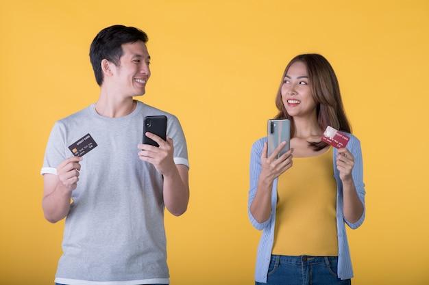 Aufgeregtes asiatisches paar, das kreditkarte und smartphone hält, das aufgeregt auf farbigem hintergrund isoliert ist