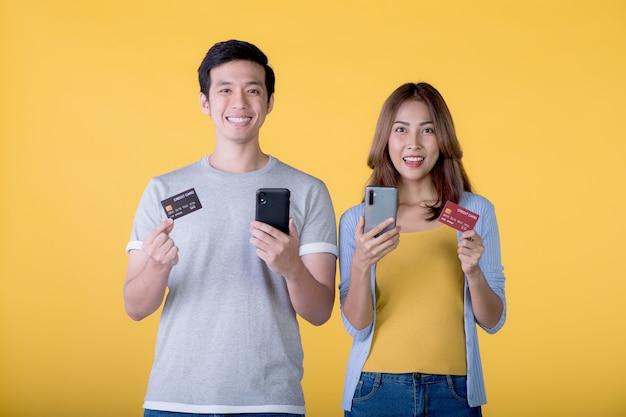 Aufgeregtes asiatisches paar, das kreditkarte und smartphone hält und sich aufgeregt fühlt, während es auf eine auf farbigem hintergrund isolierte kamera schaut