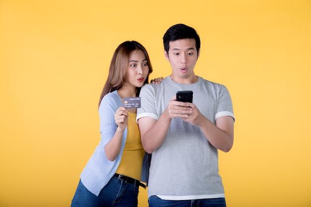 Aufgeregtes asiatisches paar, das kreditkarte und smartphone hält und sich aufgeregt fühlt, während es ein mobiltelefon einzeln auf farbigem hintergrund betrachtet