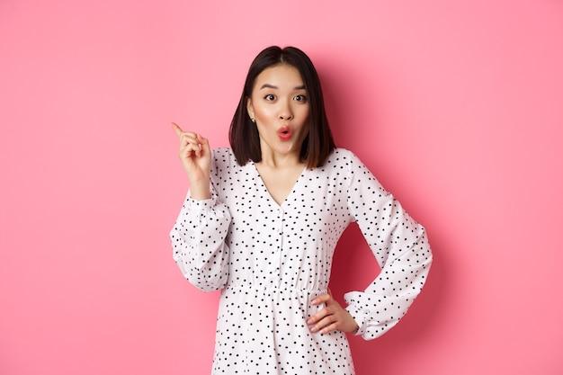 Aufgeregtes asiatisches weibliches model, das promo-angebot zeigt, das auf die obere linke ecke zeigt und in die kamera starrt ...