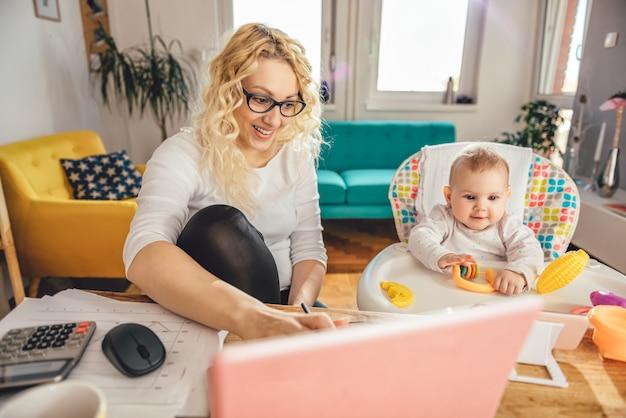 Aufgeregtes baby, das intelligentes telefon aufpasst