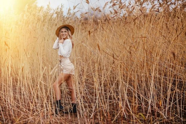 Aufgeregtes blondes glückliches safariartmädchen in einem strohhut geht auf natur unter den schilfen.