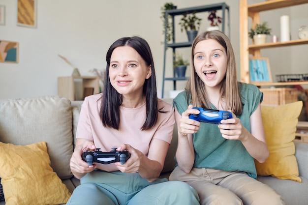 Aufgeregtes blondes teenager-mädchen mit joystick, das auf der couch neben der glücklichen mutter sitzt, während beide zu hause videospiele vor dem fernseher spielen