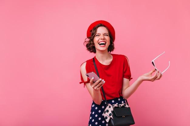 Aufgeregtes brünettes mädchen im niedlichen roten baskenmützenlachen. positives französisches weibliches modell mit lächelndem telefon in der hand.
