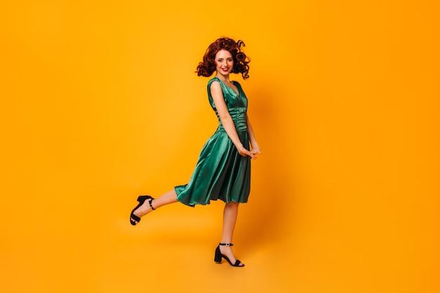 Aufgeregtes fit mädchen im grünen kleid, das auf einem bein steht. ansicht in voller länge von anmutiger dame, die auf gelbem raum tanzt.