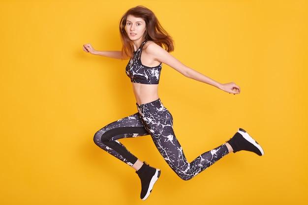 Aufgeregtes fitnessmädchen, das stilvolles sportbekleidespringen der freude trägt, isoliert auf gelb, mit ernstem gesichtsausdruck. fitness, sport ein gesundes lifestyle-konzept.