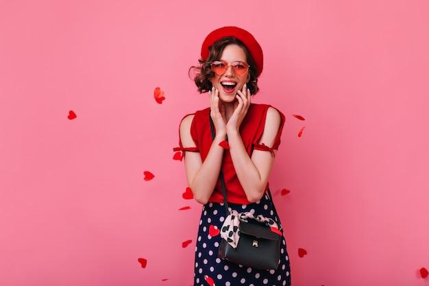 Aufgeregtes französisches mädchen mit schwarzer handtasche, die glück am valentinstag ausdrückt. fröhliche weiße dame trägt trendige baskenmütze.