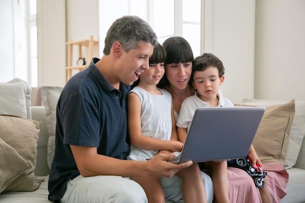 Aufgeregtes fröhliches elternpaar, das kinder auf dem schoß hält, alle zusammen auf der couch sitzt, film oder video auf laptop zu hause sieht und auf anzeige zeigt.