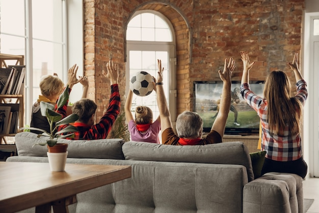 Aufgeregtes, fröhliches großes familienteam sieht sport auf der couch zu hause zusammen