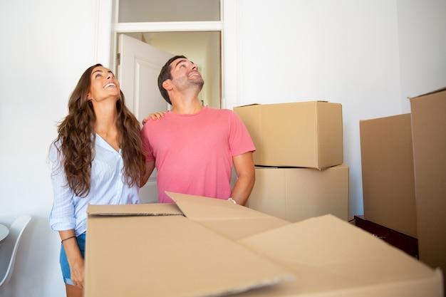 Aufgeregtes fröhliches paar, das über ihre neue wohnung schaut, zwischen stapeln von kartons steht und sich umarmt