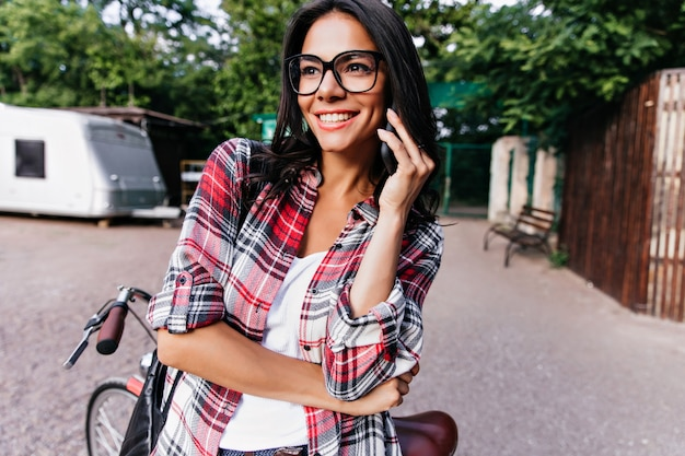 Aufgeregtes gebräuntes mädchen, das auf der straße am telefon spricht und lacht. glückselige dunkelhaarige dame, die mit smartphone posiert, während sie nahe fahrrad steht.