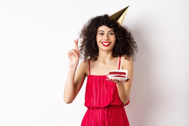Aufgeregtes geburtstagskind, das feiert, wunsch macht, kuchen hält und finger kreuzt, viel glück, glücklich auf weißem hintergrund stehend.