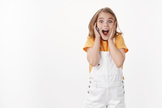 Aufgeregtes, glückliches, emotionales junges mädchen mit blonden kurzen haaren trägt sommeroveralls, berührt die wange, hört fasziniert unglaublich tolle nachrichten, hält handy, ruft freund über smartphone an