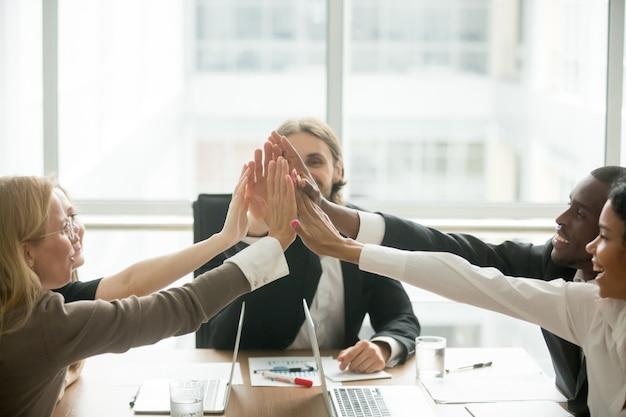 Aufgeregtes glückliches gemischtrassiges geschäftsteam, das hoch fünf bei der bürositzung gibt