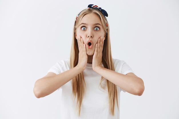 Aufgeregtes glückliches junges blondes mädchen, das gegen die weiße wand aufwirft
