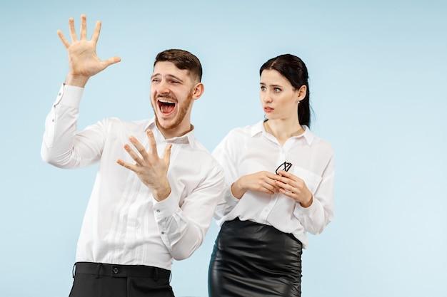 Aufgeregtes glückliches junges paar, das kamera mit freude betrachtet. geschäftsmann und frau lokalisiert auf blauem studiohintergrund