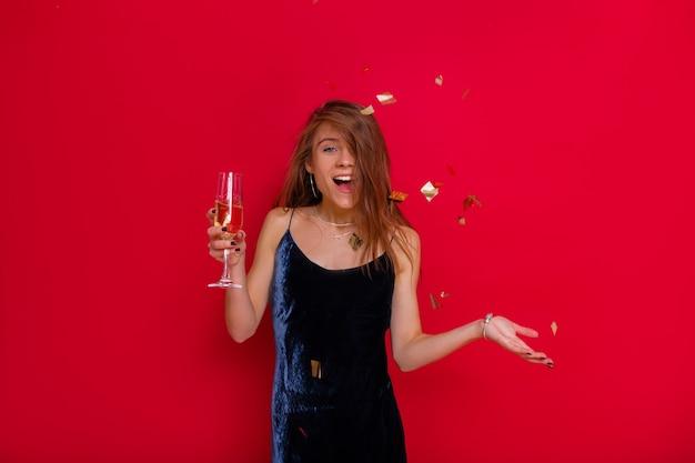 Aufgeregtes glückliches mädchen, das partykleid trägt, das über roter wand mit champagner und fliegendem konfetti aufwirft